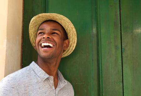 hombre con sombrero: Cerca de retrato de un hombre afroamericano feliz que r�e y que mira lejos