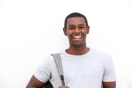 Close up portrait of a happy black college student smiling against isolated white background
