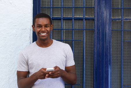 black blue: Portrait of a smiling guy holding mobile phone outside