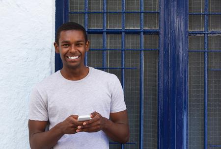 juventud: Retrato de un hombre sonriente que sostiene el teléfono móvil fuera