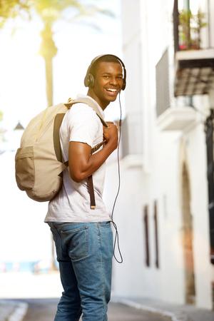 hombres negros: Retrato de un hombre joven feliz que viaja con el bolso y los auriculares