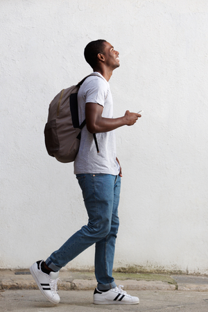 person walking: Full body side portrait of a smiling male college student walking with bag and mobile phone Stock Photo
