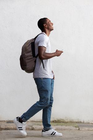 personas caminando: Retrato del lado del cuerpo de un estudiante universitario de sexo masculino sonriente caminando con bolsa y el tel�fono m�vil