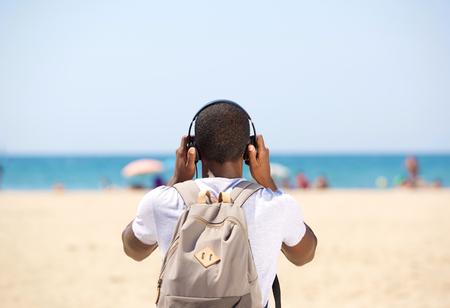 audifonos: Hombre joven con los auriculares y la bolsa de pie en la playa desde atr�s