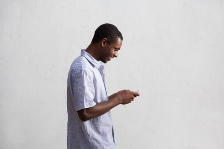 one man: Side portrait of a smiling black guy walking and using mobile phone