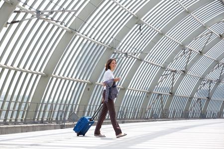mujer con maleta: Retrato de la cara de una mujer de negocios sonriente caminando con bolsa en la estación