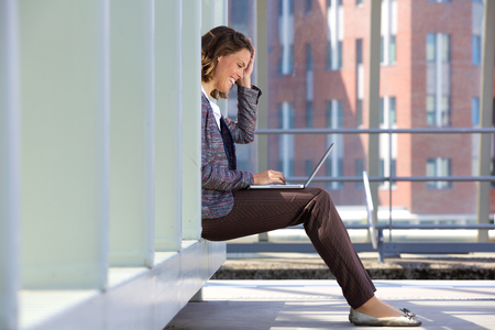 laptop outside: Side view of a happy business woman sitting outside using laptop