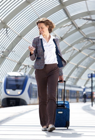 wireless woman work working: Full body portrait of a traveling business at train station