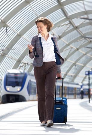 mujer con maleta: Retrato de cuerpo entero de un negocio que viaja en la estaci�n de tren