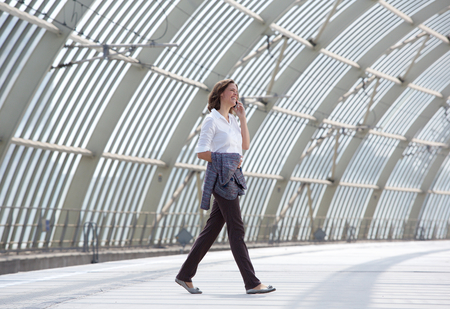 happy workers: Full body side portrait of a smiling business woman walking and talking on mobile phone