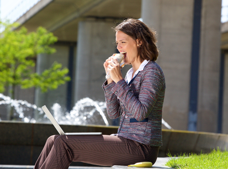 adult sandwich: Side portrait of a business woman eating food during lunch break