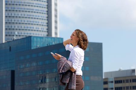 Retrato, frente, lado, sorrindo, negócio, mulher, andar, cidade, móvel, telefone Imagens