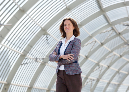 confident business woman: Portrait of a confident business woman standing with arms crossed Stock Photo