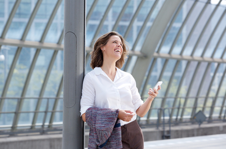 mobile business: Portrait of a smiling business woman with mobile phone looking away Stock Photo