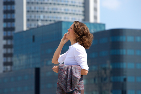 view woman: Side portrait of a business woman walking and talking on cell phone in the city Stock Photo