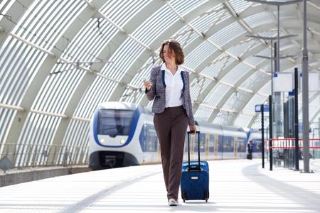 バッグと携帯電話と一緒に歩いている旅行ビジネス女性の完全な長さの肖像画