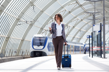 estacion de tren: Retrato de cuerpo entero de una mujer de negocios itinerante recorre con el bolso y el teléfono Foto de archivo
