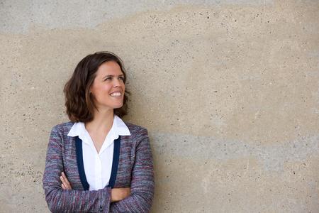 mujer trabajadora: Close up retrato de una sonriente mujer de negocios de pie con los brazos cruzados mirando a otro lado