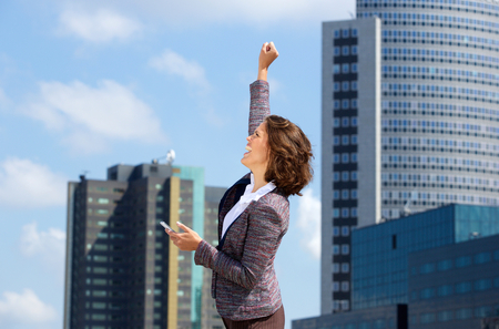 women business: Cheerful business woman punching the air with good news