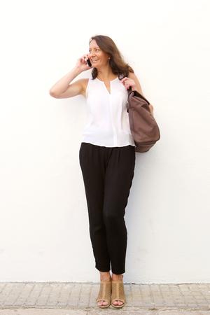 mujer cuerpo completo: Carrocería completa sonriente mujer mayor hablando por teléfono móvil