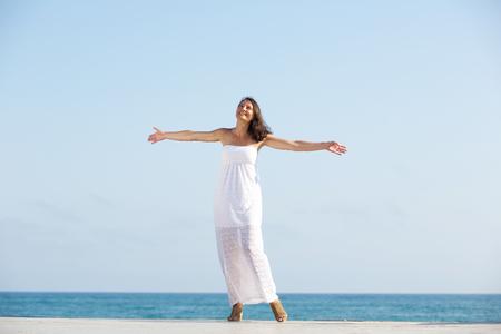 mujer alegre: Retrato de una mujer sin preocupaciones disfrutando de la vida, de pie al aire libre con los brazos extendidos