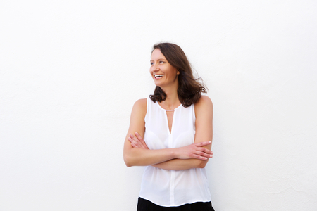 Cheerful older woman laughing with arms folded against white background