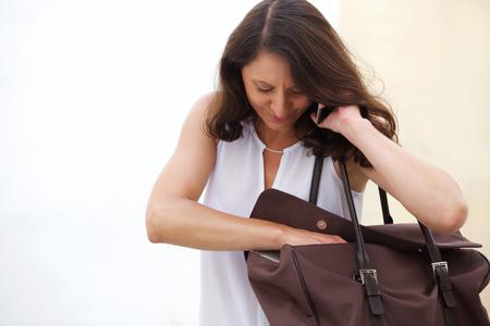 Portrait einer älteren Frau auf Handy zu hören und in der Tasche suchen