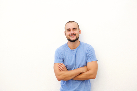 men standing: Charming young man smiling against white background with arms crossed