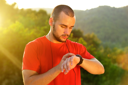 preparation: Close up young sports man checking time on watch after workout