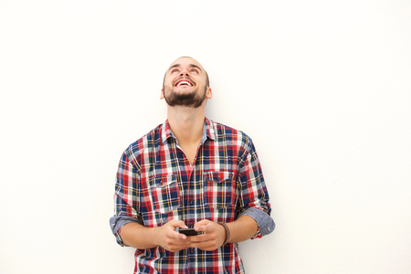 personas mirando: Apuesto joven riendo con tel�fono m�vil sobre fondo blanco Foto de archivo