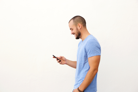 young man short hair: Handsome man with beard walking with mobile phone against white background