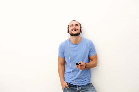 Portrait of a smiling young man with mobile phone and headphones