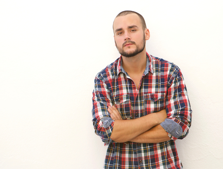 young man short hair: Modern guy with short hair and beard standing with arms crossed against white background Stock Photo