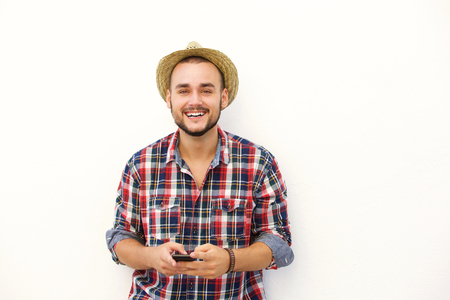 cool man: Cool young man with hat smiling with cell phone against white background