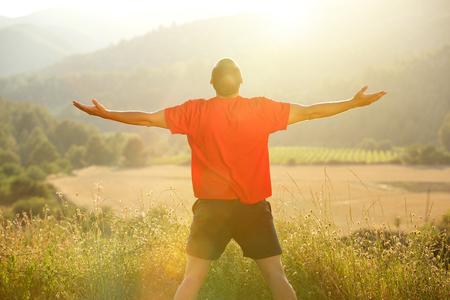 atleta corriendo: Joven de pie en la naturaleza con los brazos extendidos durante el atardecer Foto de archivo