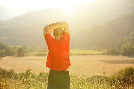 back exercise: Young man standing in countryside stretching exercise before workout