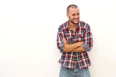 riendo: Hombre joven que ríe y que mira lejos de pie contra el fondo blanco con los brazos cruzados