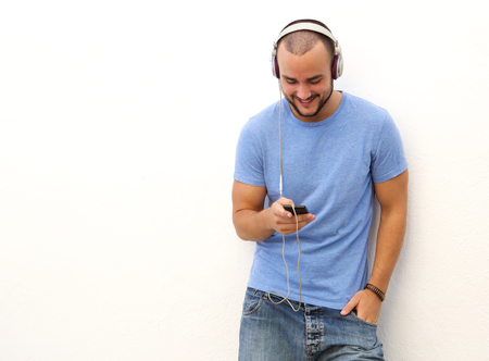 man searching: Portrait of a smiling man standing against a white wall with mobile phone and headphones Stock Photo