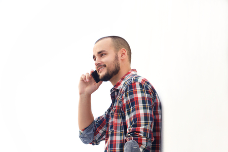 a beard: Side portrait of a smiling modern man with short hair and beard using mobile phone