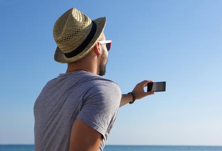 hombre con sombrero: Hombre joven que toma autofoto con el tel�fono m�vil por el mar
