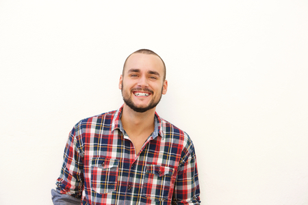 Close up happy hispanic guy in plaid shirt smiling against white background