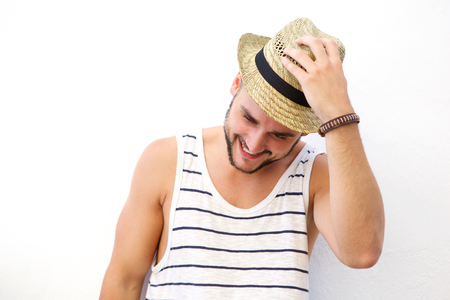 casual fashion: Close up portrait of a young man laughing with hat against white background