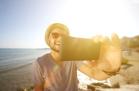 vacaciones en la playa: Hombre feliz en vacaciones tomando un selfie en la playa