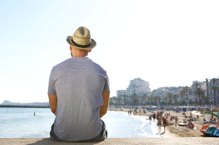 Portrait from behind of a man sitting alone looking at the beach in summer Stok Fotoğraf
