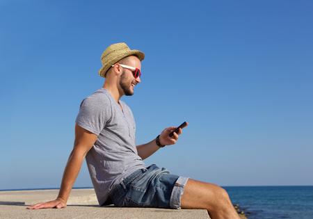 hombre con sombrero: Retrato lateral de un joven feliz que se sienta por el mar con el teléfono móvil