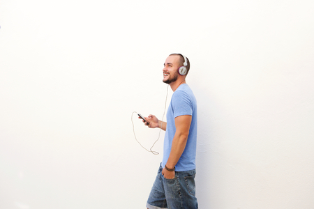 Happy man walking with mobile phone listening to music on headphones Imagens