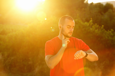 shape: Sports man checking pulse and looking at watch during sunset