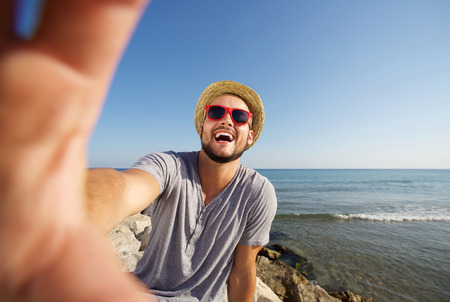 beach: Happy man on vacation laughing at the beach taking selfie