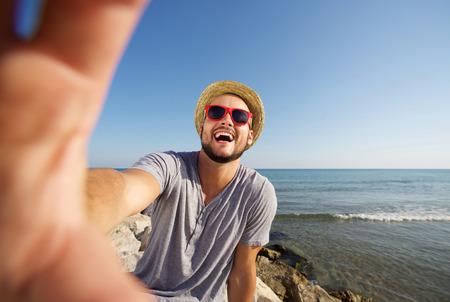hombre con sombrero: Hombre feliz en vacaciones riéndose de la toma playa selfie