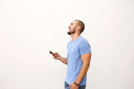 young man short hair: Cheerful young man walking with mobile phone against white background Stock Photo